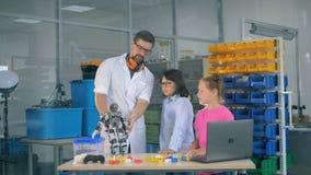De mannelijke onderzoekvennoot toont twee jonge geitjes hoe een robot werkt stock video