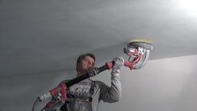 De mannelijke oppervlakte van de bouwvakker gladmakende muur met schuurmachine stock video