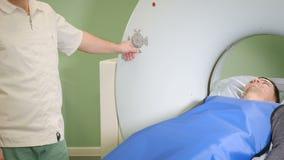 De mannelijke patiënt beweegt zich in een CT-Scanner Medische apparatuur: gegevens verwerkte tomografiemachine in kenmerkende kli stock videobeelden