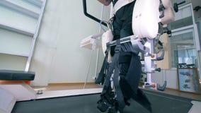 De mannelijke patiënt met fysieke impairments oefent op een het lopen spoorsimulator uit Elektronische medische robotachtig voor stock video
