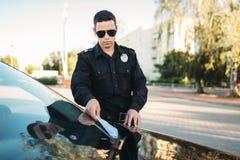 De mannelijke politieagent in eenvormig schrijft een boete op weg stock foto's