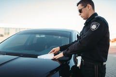 De mannelijke politieagent in eenvormig schrijft een boete op weg royalty-vrije stock afbeelding