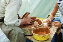 De mannelijke pottenbakker onderwijst een kind hoe te van klei te vormen stock afbeelding