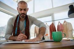 De mannelijke schets van de ontwerpertekening terwijl het zitten bij lijst stock fotografie