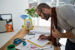 De mannelijke schets van de ontwerpertekening terwijl status bij lijst royalty-vrije stock foto