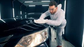 De mannelijke specialist gebruikt een doek om een auto te verglazen stock footage
