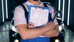 De mannelijke specialist met hulpmiddelen en een klembord bevindt zich voor een auto De autodienst, het autoconcept van de autore stock footage