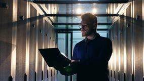 De mannelijke IT specialist stelt laptop in een serverruimte in werking stock footage