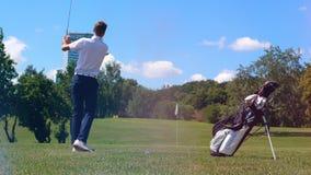 De mannelijke speler raakt de golfbal met sterkte stock footage