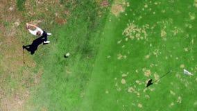 De mannelijke speler slaat een golfbal met sterkte in een hoogste mening stock footage