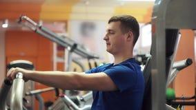 De mannelijke spieren die van de opleidingsborst oefeningsmachine voor lichaamsmassa met behulp van Gewicht het duwen stock footage
