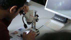 De mannelijke student met glazen kijkt door een verlichte microscoop, vergroot die beeld op het scherm wordt getoond stock video