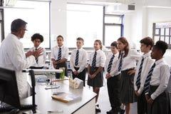 De mannelijke Studenten die van Teaching High School van de Middelbare schoolprivé-leraar Uniformen in Wetenschapsklasse dragen stock fotografie