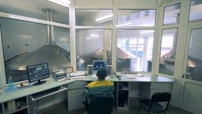 De mannelijke technicus controleert alcohol-producerend proces van zijn bureau stock footage