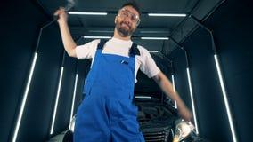 De mannelijke technicus voor de gek houdt rond het houden van mechanische hulpmiddelen stock video