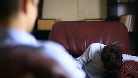 De mannelijke therapeut leidt een psychologisch overleg met een tiener Jongenstiener bij de ontvangst van a stock footage