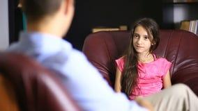 De mannelijke therapeut leidt een psychologisch overleg met een tiener Meisjestiener bij een ontvangst met een psycholoog stock video