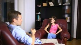De mannelijke therapeut leidt een psychologisch overleg met een tiener Meisjestiener bij een ontvangst met een psycholoog stock footage