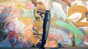 De mannelijke tiener heft een skateboard met zijn been op stock footage