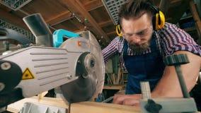 De mannelijke timmerman gebruikt een roterende zaag in zijn workshop stock footage