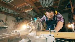 De mannelijke timmerman verwerkt hout met een roterende zaag stock videobeelden
