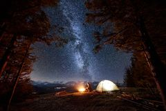De mannelijke toerist heeft een rust in zijn kamp dichtbij het bos bij nacht onder het mooie hoogtepunt van de nachthemel van ste stock fotografie