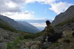 De mannelijke toerist zit in de bergen van de Barguzin-rand bij Meer Royalty-vrije Stock Foto's