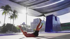 De mannelijke turner leidt op trampoline op Mens springen openlucht in langzame motie stock video