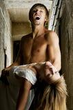 De mannelijke vampier gaat een jonge vrouw bijten stock afbeelding
