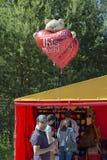 De mannelijke verkoper houdt hart-vormige ballons in zijn hand stock afbeeldingen
