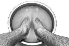De mannelijke voeten in een bassin met mosterd stijgt zijn benen, op een witte natuurlijke achtergrond stock foto