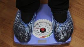 De mannelijke voeten in schoen behandelt het stappen op blauwe schalen bij het ziekenhuis, close-up stock video