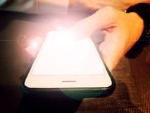 De mannelijke volwassen hand van ` s houdt witte persoonlijke smartphone met helderheid en gloed op het scherm stock afbeelding