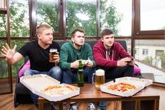 De mannelijke vrienden die videospelletjes spelen, drinken bier en hebben thuis pret Royalty-vrije Stock Afbeelding