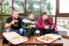 De mannelijke vrienden die videospelletjes spelen, drinken bier en hebben thuis pret Stock Foto's