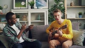 De mannelijke vrienden hebben pret thuis, speelt de Kaukasische kerel de gitaar en de Afrikaanse Amerikaanse jonge mens registree stock footage