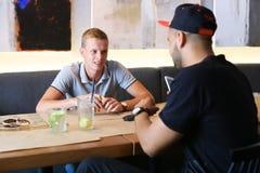 De mannelijke vrienden in koffiebespreking bespreken met de tablet van de technologietelefoon Royalty-vrije Stock Foto