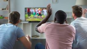 De mannelijke vrienden verzamelen zich om de voetbal op concurrentie op het grote scherm, bankdeskundigen te letten stock video