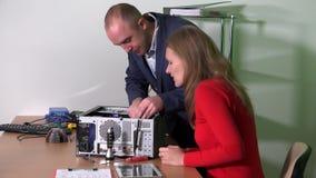 De mannelijke vrouwelijke collega van de zakenmanhulp aan reparatiecomputer stock video