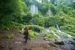De mannelijke wandelaar geniet de waterval van mening van Benang Kelambu stock afbeelding