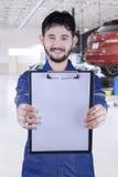 De mannelijke werktuigkundige toont klembord in workshop Royalty-vrije Stock Fotografie