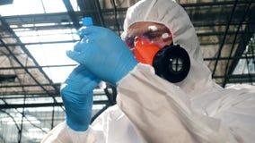 De mannelijke wetenschapper bekijkt de buis met chemische producten stock video