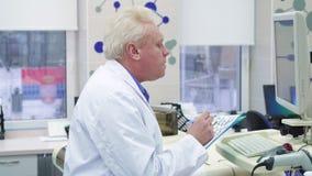 De mannelijke wetenschapper neemt nota van informatie over klembord bij het laboratorium stock footage