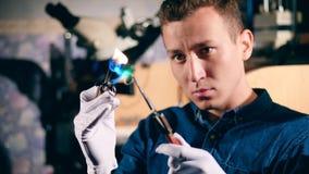 De mannelijke zilversmid brandt het kader van de zilveren ring De juwelier maakt een stuk van juwelen stock video