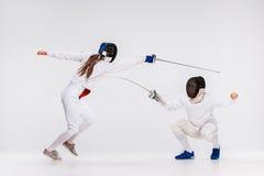 De mannen en de vrouw die het schermen kostuum het praktizeren met zwaard dragen tegen grijs Stock Fotografie