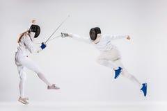 De mannen en de vrouw die het schermen kostuum het praktizeren met zwaard dragen tegen grijs Stock Foto