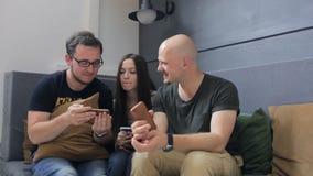 De mannen en de vrouw kijken door beeld in celtelefoon stock footage