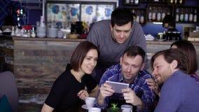De mannen en de vrouwen van middenleeftijd willen een gezamenlijke foto voor geheugen maken, zit het bedrijf in een restaurant en stock video