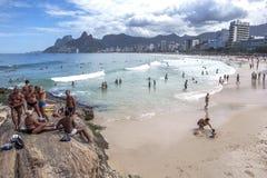 De mannen en de vrouwen zitten op een rotsdagzomende aardlaag boven Ipanema-Strand in Rio de Janeiro in Brazilië Royalty-vrije Stock Afbeeldingen