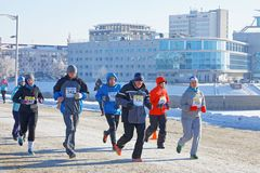 De mannen en de vrouw met dikke rijp op hun hoeden lopen tijdens de Kerstmis helft-marathon in Omsk bij minus 23 Royalty-vrije Stock Foto's